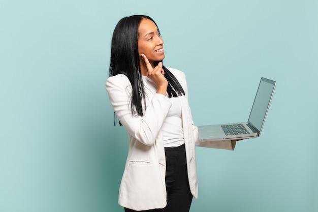 Młoda czarna kobieta uśmiecha się radośnie i marzy lub wątpi, patrząc w bok. koncepcja laptopa