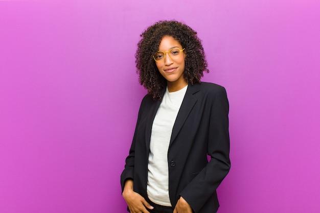 Młoda czarna kobieta uśmiecha się radośnie i od niechcenia z pozytywnym, szczęśliwym, pewnym siebie i zrelaksowanym wyrazem twarzy