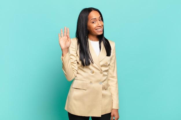 Młoda czarna kobieta uśmiecha się radośnie i radośnie, machając ręką, witając cię i witając lub żegnając się