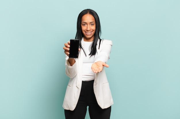 Młoda czarna kobieta uśmiecha się radośnie z przyjaznym, pewnym siebie, pozytywnym spojrzeniem, oferując i pokazując przedmiot lub koncepcję. koncepcja inteligentnego telefonu