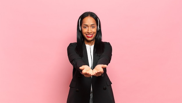 Młoda czarna kobieta uśmiecha się radośnie z przyjaznym, pewnym siebie, pozytywnym spojrzeniem, oferuje i pokazuje przedmiot lub koncepcję. koncepcja telemarketingu