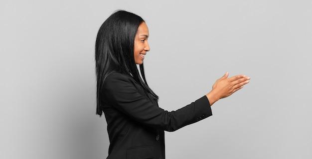Młoda czarna kobieta uśmiecha się, wita cię i oferuje uścisk dłoni, aby zamknąć udaną transakcję, koncepcja współpracy. pomysł na biznes