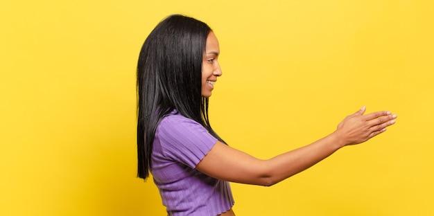 Młoda czarna kobieta uśmiecha się, wita cię i oferuje uścisk dłoni, aby zamknąć udaną transakcję, koncepcja współpracy