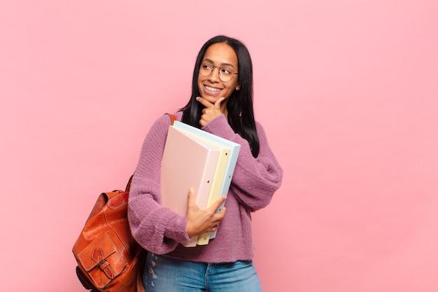 Młoda czarna kobieta uśmiecha się z radosnym, pewnym siebie wyrazem z ręką na brodzie, zastanawia się i patrzy w bok. koncepcja studenta