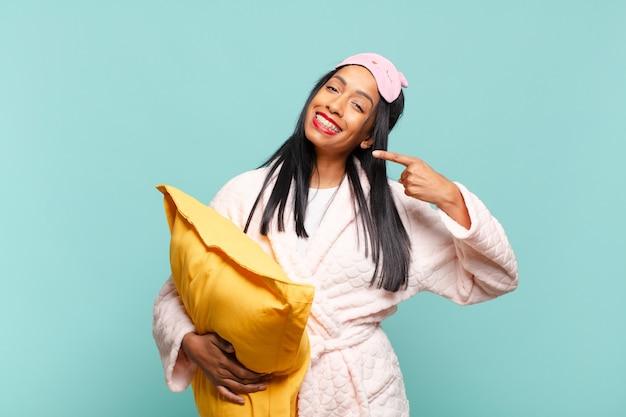 Młoda czarna kobieta uśmiechając się pewnie wskazując na swój szeroki uśmiech, pozytywną, zrelaksowaną, zadowoloną postawę. koncepcja piżamy