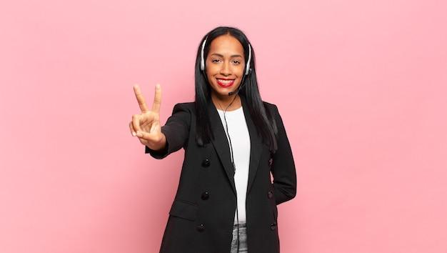 Młoda czarna kobieta uśmiechnięta i wyglądająca na szczęśliwą, beztroską i pozytywną, gestem zwycięstwa lub pokoju jedną ręką. koncepcja telemarketingu
