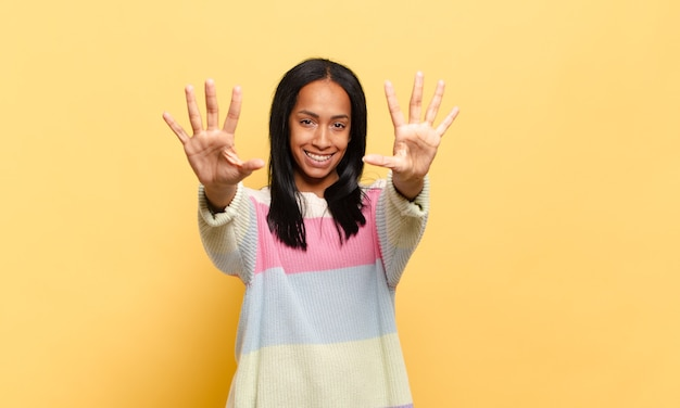 Młoda czarna kobieta uśmiechnięta i wyglądająca przyjaźnie, pokazująca liczbę dziesięć lub dziesiątą ręką do przodu, odliczając w dół