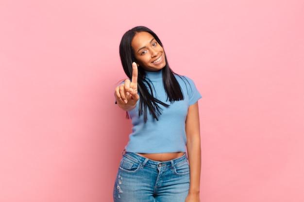 Młoda czarna kobieta uśmiechnięta i wyglądająca przyjaźnie, pokazująca numer jeden lub pierwszy z ręką do przodu, odliczająca