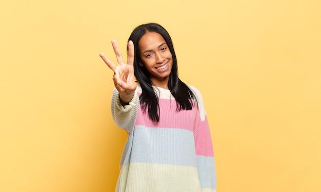 Młoda czarna kobieta uśmiechnięta i wyglądająca przyjaźnie, pokazująca numer trzy lub trzeci z ręką do przodu, odliczający