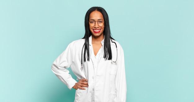 Młoda czarna kobieta uśmiechnięta radośnie z ręką na biodrze i pewna siebie, pozytywna, dumna i przyjazna postawa. koncepcja lekarza