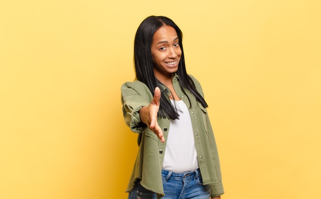 Młoda czarna kobieta uśmiechnięta, wyglądająca na szczęśliwą, pewną siebie i przyjazną, oferująca uścisk dłoni w celu zawarcia umowy, współpracująca