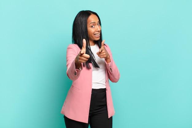 Młoda czarna kobieta uśmiechnięta z pozytywnym, udanym, szczęśliwym nastawieniem, wskazując na kamerę, robiąc znak pistoletu rękami. pomysł na biznes