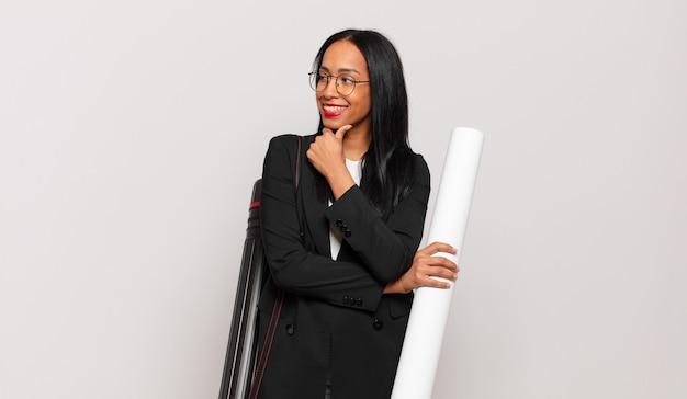 Młoda czarna kobieta uśmiechnięta ze szczęśliwym, pewnym siebie wyrazem twarzy z ręką na brodzie, zastanawiająca się i patrząca w bok. koncepcja architekta