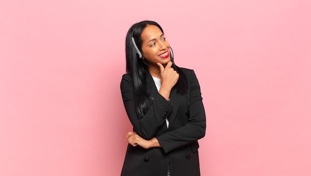 Młoda czarna kobieta uśmiechnięta ze szczęśliwym, pewnym siebie wyrazem twarzy z ręką na brodzie, zastanawiająca się i patrząca w bok. koncepcja telemarketingu
