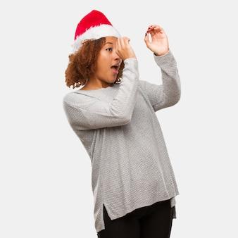Młoda czarna kobieta w kapeluszu santa podejmowania gest spyglass