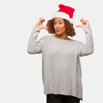 Młoda czarna kobieta w kapeluszu santa wskazując palcami, przykład do naśladowania