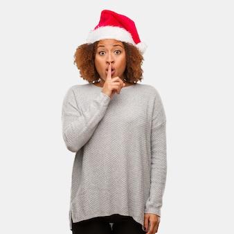 Młoda czarna kobieta w kapeluszu santa zachowując tajemnicę lub prosząc o ciszę