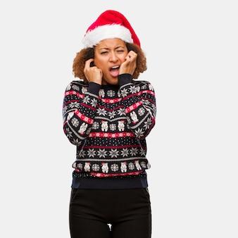 Młoda czarna kobieta w modny sweter christmas z nadrukiem obejmujące uszy rękoma