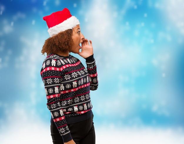 Młoda czarna kobieta w modny sweter christmas z nadrukiem szeptem podszeptu