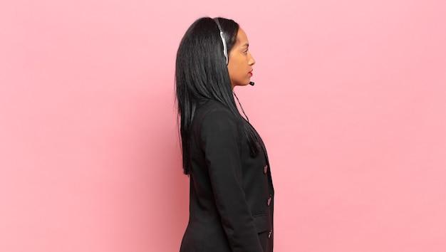 Młoda czarna kobieta w widoku profilu, chcąca skopiować przestrzeń do przodu, myśląc, wyobrażając sobie lub marząc na jawie