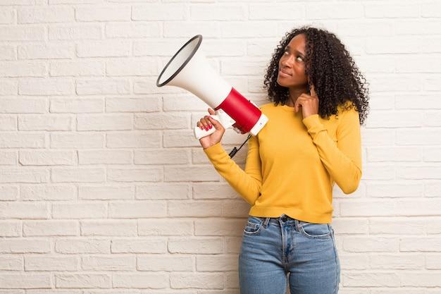 Młoda czarna kobieta wątpić i mylić, myśląc o idei lub martwi się o coś