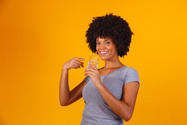 Młoda czarna kobieta woda pitna na kolor żółty. młoda dziewczyna ze szklanką wody