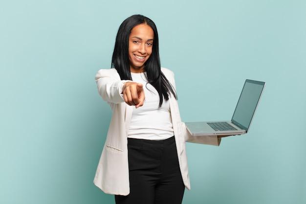 Młoda czarna kobieta, wskazując na aparat z zadowolonym, pewnym siebie, przyjaznym uśmiechem, wybierająca ciebie. koncepcja laptopa