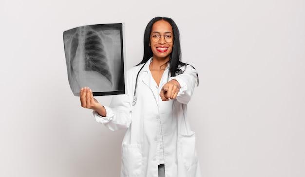 Młoda czarna kobieta wskazująca z zadowolonym, pewnym siebie, przyjaznym uśmiechem, wybierająca ciebie. koncepcja lekarza