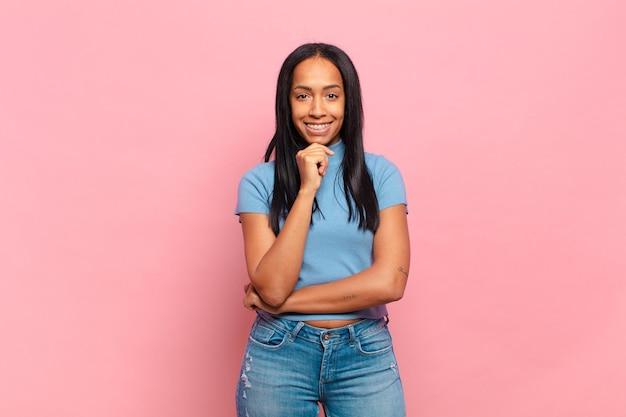 Młoda czarna kobieta wygląda na szczęśliwą i uśmiecha się z ręką na brodzie, zastanawia się lub zadaje pytanie, porównując opcje