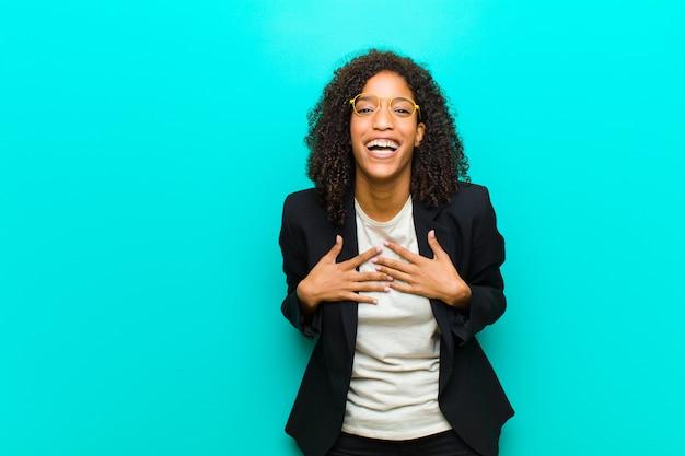 Młoda czarna kobieta wygląda na szczęśliwą, zaskoczoną, dumną i podekscytowaną, wskazując na siebie