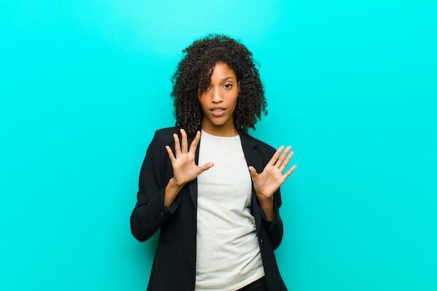 Młoda czarna kobieta wygląda na zdenerwowaną, niespokojną i zaniepokojoną, mówiąc, że to nie moja wina, albo nie zrobiłem tego przeciw niebieskiej ścianie