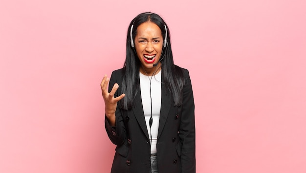 Młoda czarna kobieta wygląda na złą, zirytowaną i sfrustrowaną krzyczącą. koncepcja telemarketingu