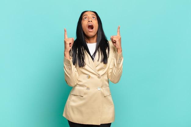 Młoda czarna kobieta wygląda na zszokowaną, zdumioną i z otwartymi ustami, wskazując w górę obiema rękami, aby skopiować przestrzeń. pomysł na biznes
