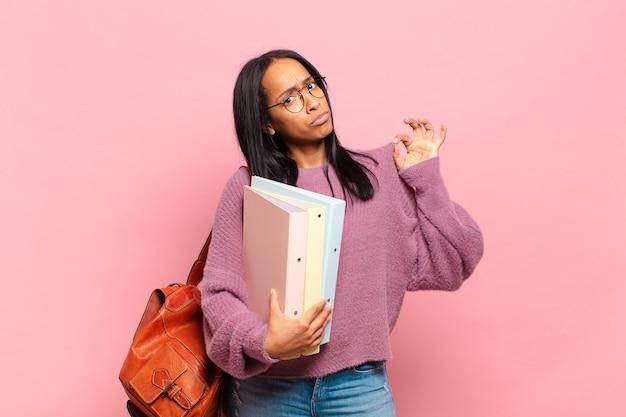 Młoda czarna kobieta wyglądająca na arogancką, odnoszącą sukcesy, pozytywną i dumną, wskazującą na siebie. koncepcja studenta