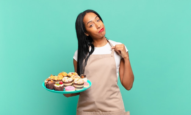 Młoda czarna kobieta wyglądająca na arogancką, odnoszącą sukcesy, pozytywną i dumną, wskazującą na siebie. koncepcja szefa kuchni piekarni