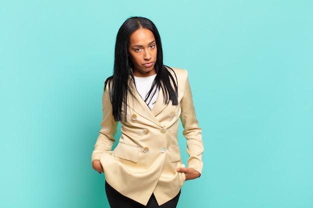 Młoda czarna kobieta wyglądająca na dumną, pewną siebie, fajną, bezczelną i arogancką, uśmiechniętą, czującą sukces. pomysł na biznes
