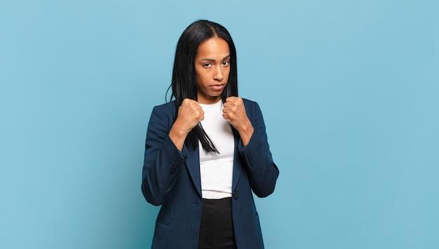 Młoda czarna kobieta wyglądająca na pewną siebie, złą, silną i agresywną, z pięściami gotowymi do walki w pozycji bokserskiej. pomysł na biznes