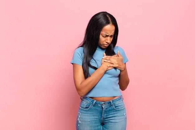 Młoda czarna kobieta wyglądająca na smutną, zranioną i załamaną