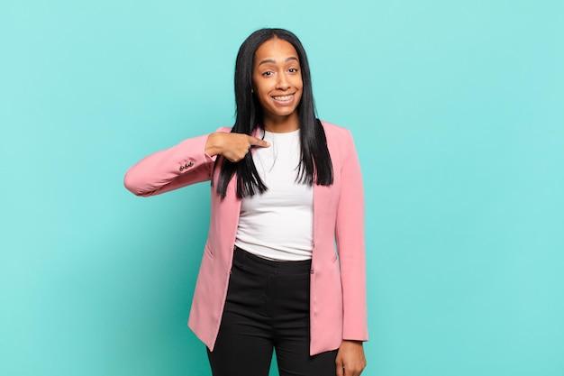 Młoda czarna kobieta wyglądająca na szczęśliwą, dumną i zaskoczoną, radośnie wskazującą na siebie, czującą się pewnie i wyniośle. pomysł na biznes