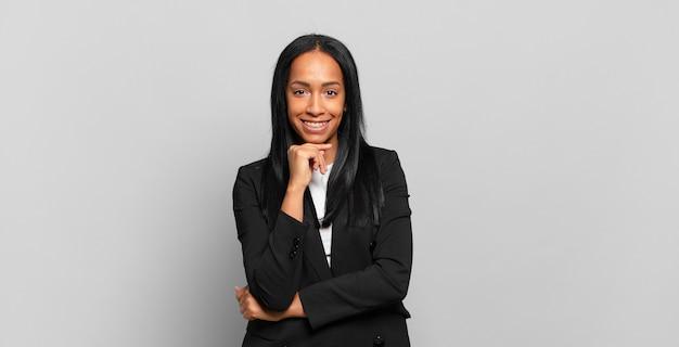 Młoda czarna kobieta wyglądająca na szczęśliwą i uśmiechnięta z ręką na brodzie, zastanawiająca się lub zadająca pytanie, porównująca opcje. pomysł na biznes