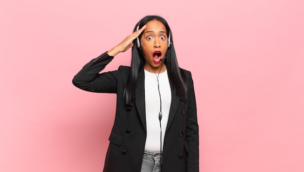 Młoda czarna kobieta wyglądająca na szczęśliwą, zdziwioną i zaskoczoną, uśmiechniętą i przekazującą niesamowite i niewiarygodnie dobre wieści. koncepcja telemarketingu