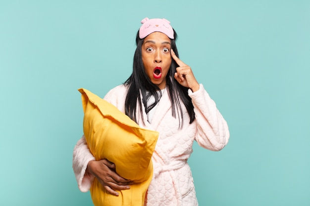 Młoda czarna kobieta wyglądająca na zaskoczoną, z otwartymi ustami, zszokowaną, realizującą nową myśl, pomysł lub koncepcję. koncepcja piżamy
