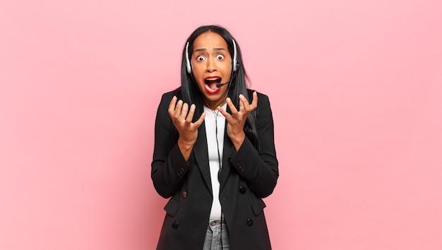 Młoda czarna kobieta wyglądająca na zdesperowaną i sfrustrowaną, zestresowaną, nieszczęśliwą i zirytowaną, krzyczącą i krzyczącą. koncepcja telemarketingu