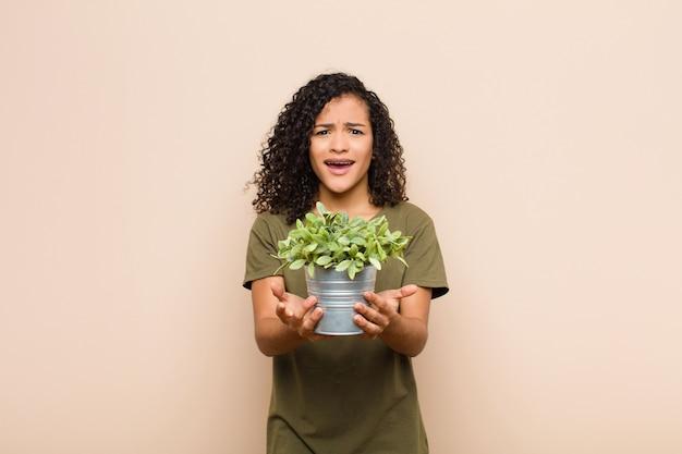 Młoda czarna kobieta wyglądająca na zdesperowaną i sfrustrowaną, zestresowaną, nieszczęśliwą i zirytowaną, krzyczącą i krzyczącą trzymającą roślinę