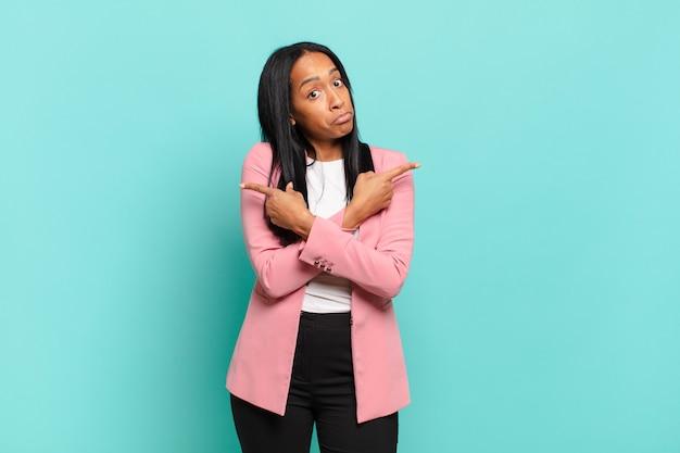 Młoda czarna kobieta wyglądająca na zdziwioną i zdezorientowaną, niepewną siebie i wskazującą w przeciwnych kierunkach z wątpliwościami. pomysł na biznes