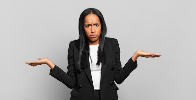 Młoda czarna kobieta wyglądająca na zdziwioną, zdezorientowaną i zestresowaną, zastanawiającą się między różnymi opcjami, czującą się niepewnie. pomysł na biznes