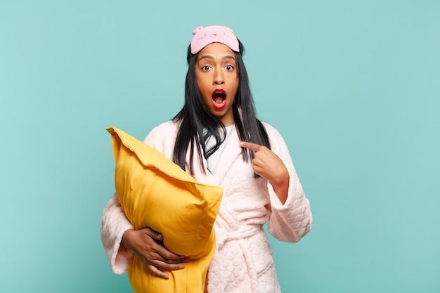 Młoda czarna kobieta wyglądająca na zszokowaną i zaskoczoną z szeroko otwartymi ustami