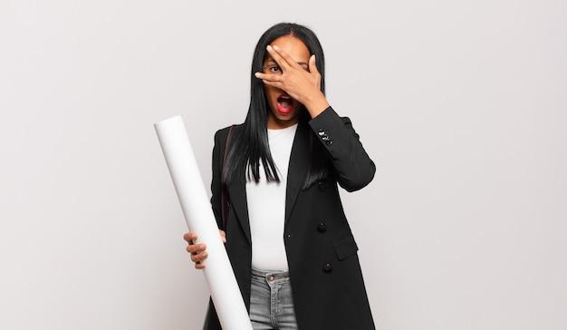 Młoda czarna kobieta wyglądająca na zszokowaną, przestraszoną lub przerażoną, zakrywa twarz dłonią i zerka między palcami. koncepcja architekta