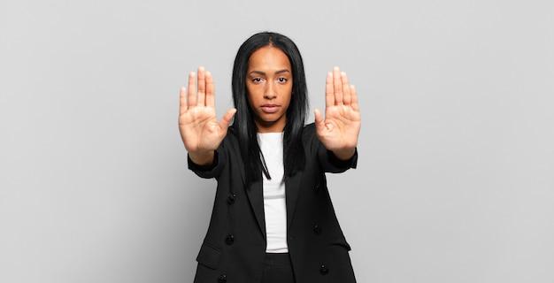 """Młoda czarna kobieta wyglądająca poważnie, nieszczęśliwa, zła i niezadowolona, zakazująca wejścia lub mówiąca """"stop"""" z obiema otwartymi dłońmi. pomysł na biznes"""
