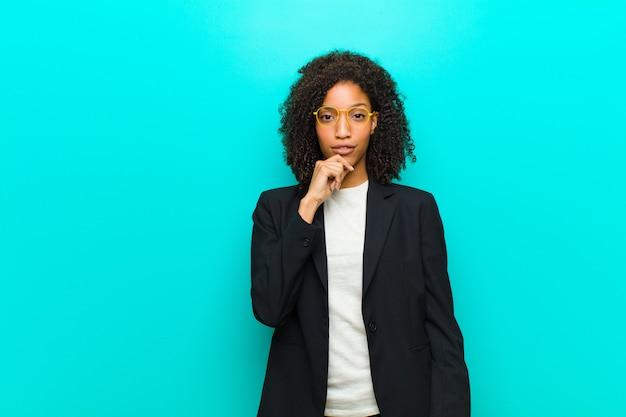 Młoda czarna kobieta wyglądająca poważnie, zdezorientowana, niepewna i zamyślona, wątpiąca w opcje i wybory na tle niebieskiej ściany